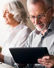Elderly couple researching pension options online